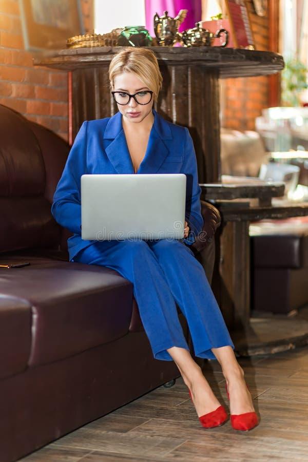Empresaria joven que trabaja la sentada en l?nea en el sof? fotografía de archivo libre de regalías