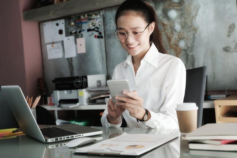 Empresaria joven que usa el teléfono elegante mientras que trabaja en ella offic foto de archivo libre de regalías
