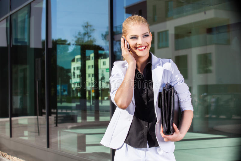 Empresaria joven que usa el teléfono móvil en la calle fotos de archivo libres de regalías