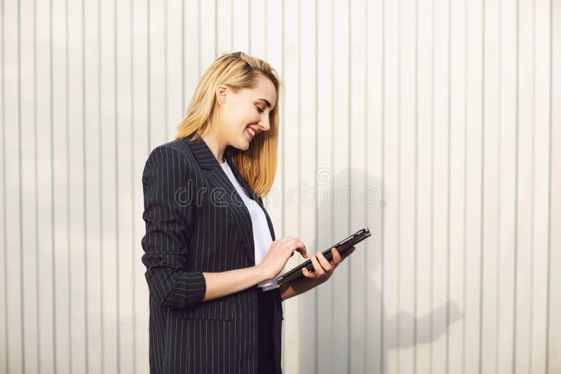 Empresaria joven que usa una tableta, durante descanso para tomar caf? al aire libre, cerca del edificio de oficinas Concepto de  imagen de archivo