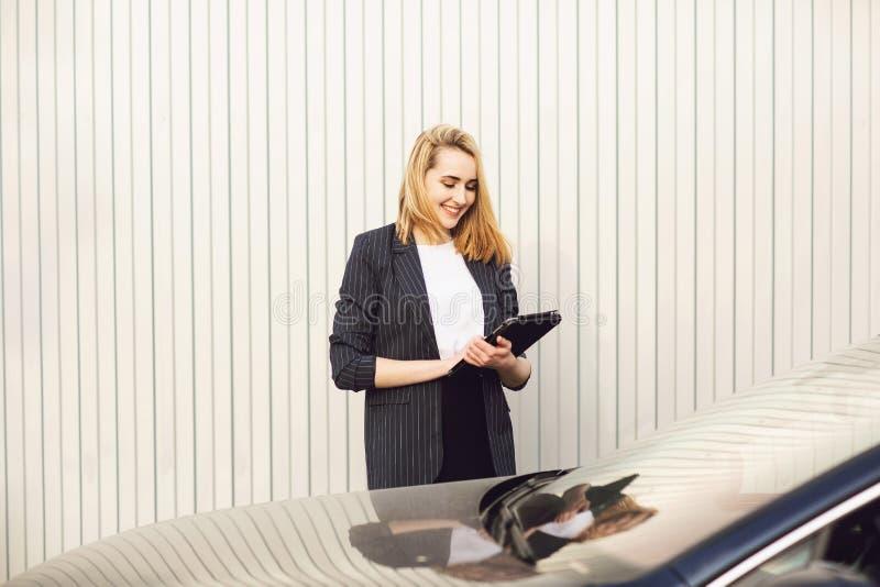 Empresaria joven que usa una tableta, durante descanso para tomar caf? al aire libre, cerca del edificio de oficinas Concepto de  fotografía de archivo