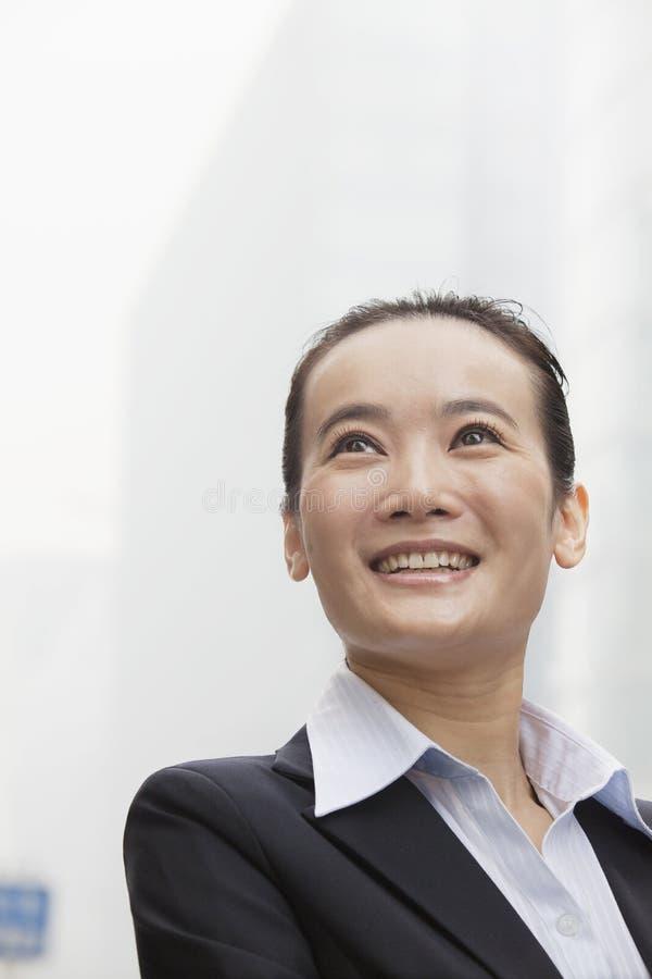 Empresaria joven Smiling y mirada en la distancia fotos de archivo