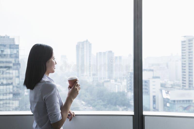 Empresaria joven sonriente que sostiene una taza de café y que mira hacia fuera la ventana el paisaje urbano en Pekín, China fotografía de archivo