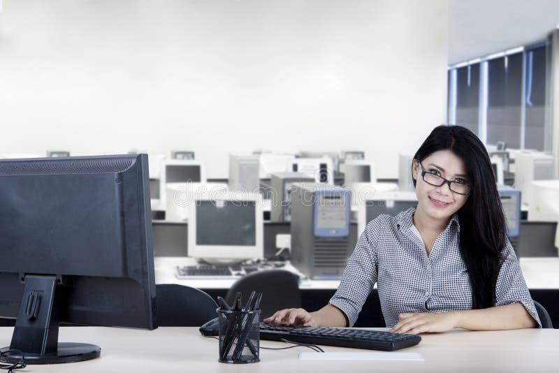 Empresaria joven sonriente que trabaja en la oficina fotos de archivo