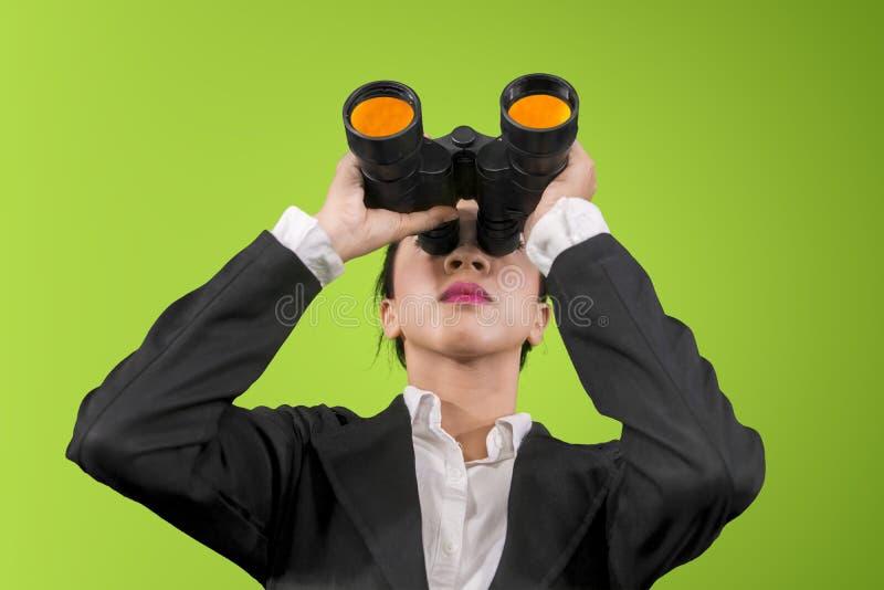 Empresaria joven usando los prismáticos en estudio imagenes de archivo