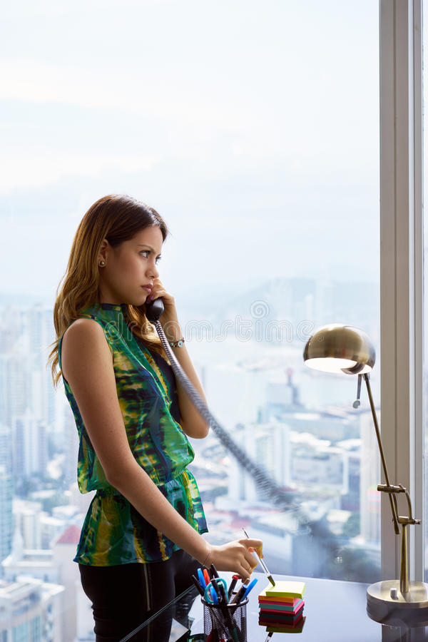 Empresaria joven With Wired Telephone de Latina en oficina moderna foto de archivo