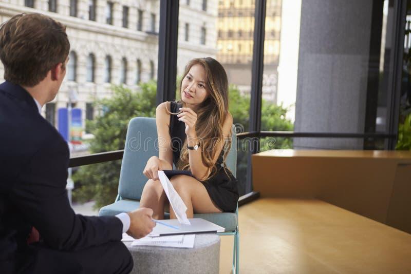 Empresaria joven y hombre que hablan en una reunión informal foto de archivo