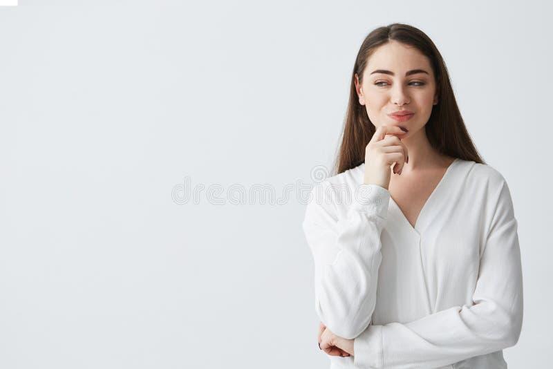 Empresaria juguetona hermosa joven con el vistazo difícil astuto que sonríe sobre el fondo blanco imagenes de archivo