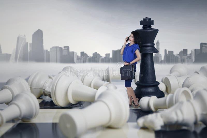 Empresaria Leaning en las figuras del ajedrez foto de archivo libre de regalías