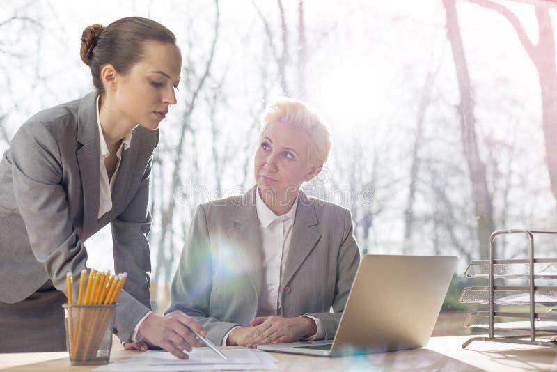 Empresaria madura confiada que mira al colega que explica el documento en el escritorio contra ventana en oficina fotos de archivo libres de regalías