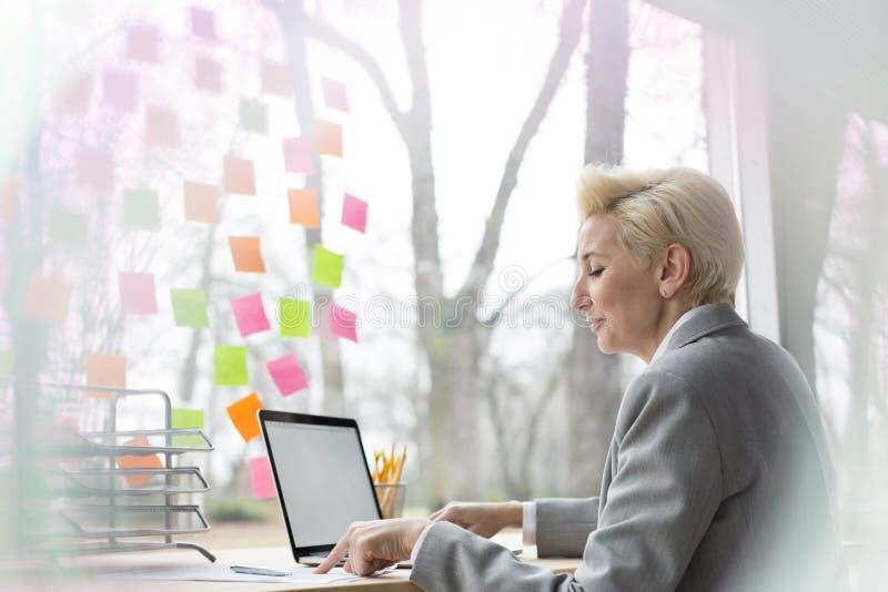 Empresaria madura confiada que usa el ordenador portátil mientras que se sienta con el documento en el escritorio en oficina imagen de archivo