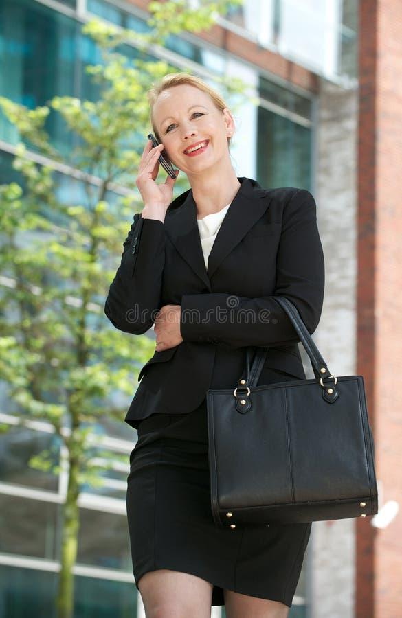 Empresaria madura que llama por el teléfono móvil en la ciudad fotos de archivo
