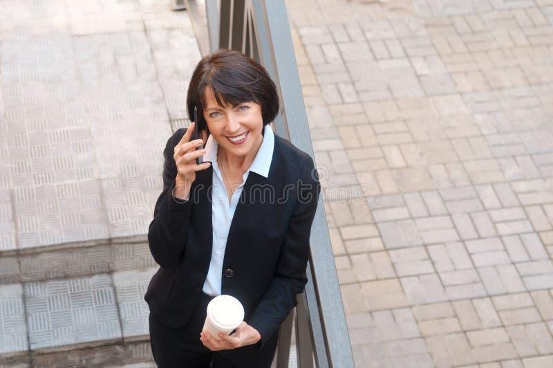 Empresaria madura que tiene una rotura delante de un edificio de oficinas, hablando en el teléfono y bebiendo el café fotografía de archivo libre de regalías