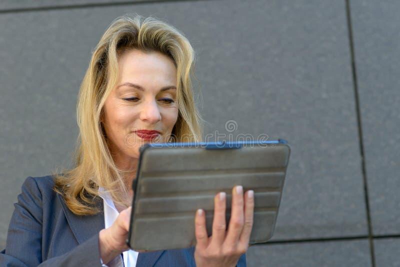 Empresaria madura que usa una tableta del PDA imágenes de archivo libres de regalías