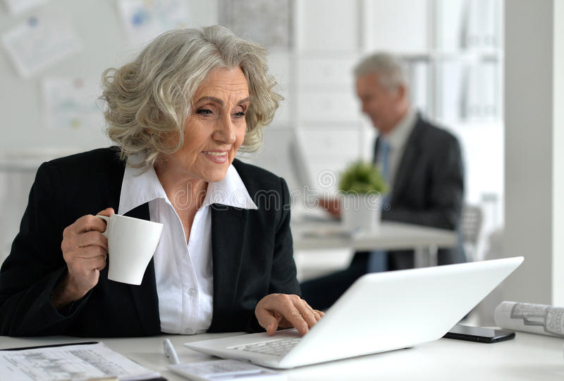 Empresaria mayor con la computadora portátil imagen de archivo
