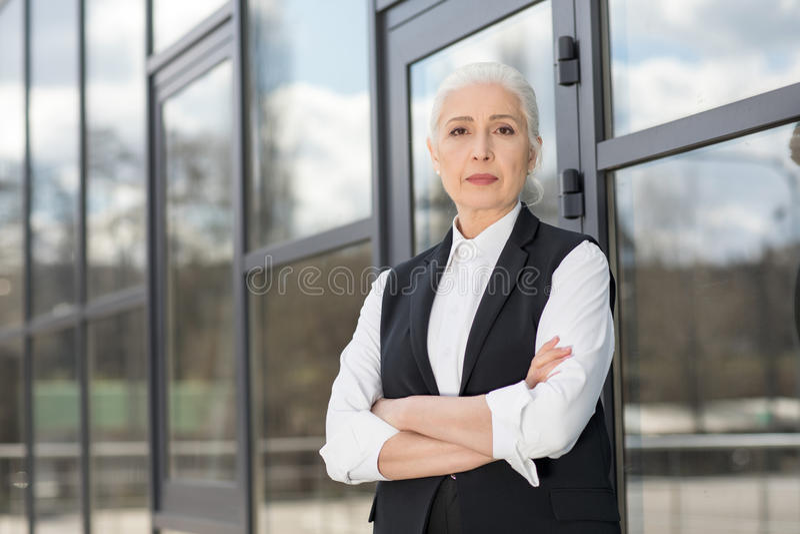 Empresaria mayor confiada hermosa que se coloca con los brazos cruzados y que mira la cámara imagen de archivo libre de regalías