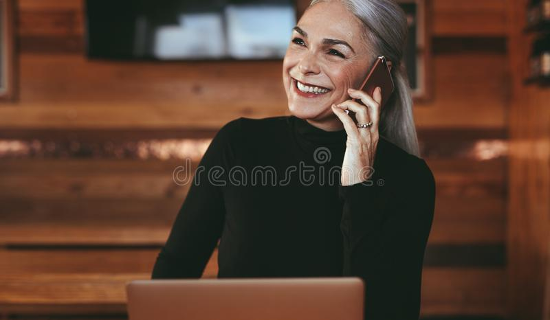 Empresaria mayor en la cafetería que hace una llamada de teléfono fotografía de archivo