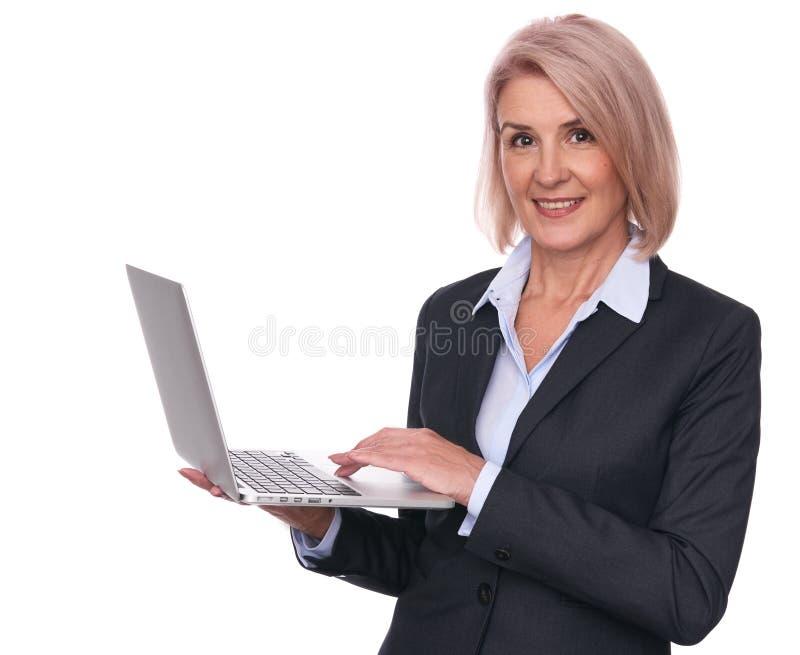 Empresaria mayor hermosa con el ordenador portátil imagen de archivo