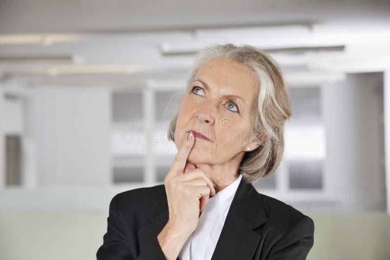 Empresaria mayor pensativa que mira para arriba en oficina imagen de archivo libre de regalías