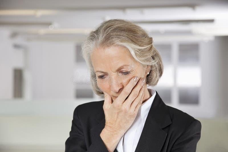 Empresaria mayor preocupante con la mano en boca en oficina imagenes de archivo