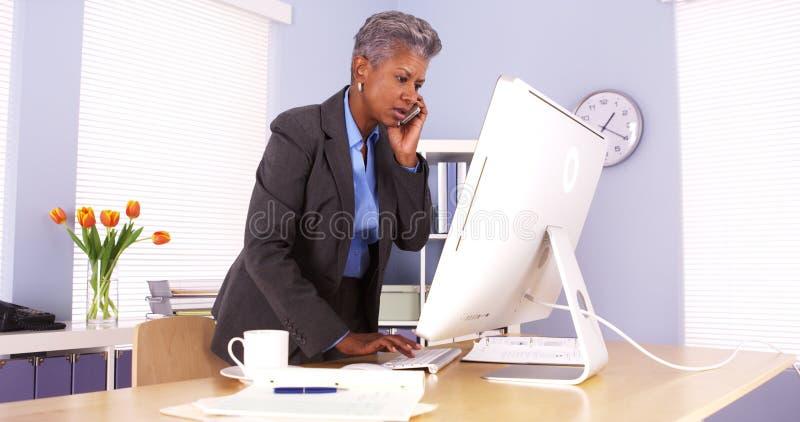 Empresaria mayor que habla en el teléfono y que trabaja en oficina fotografía de archivo