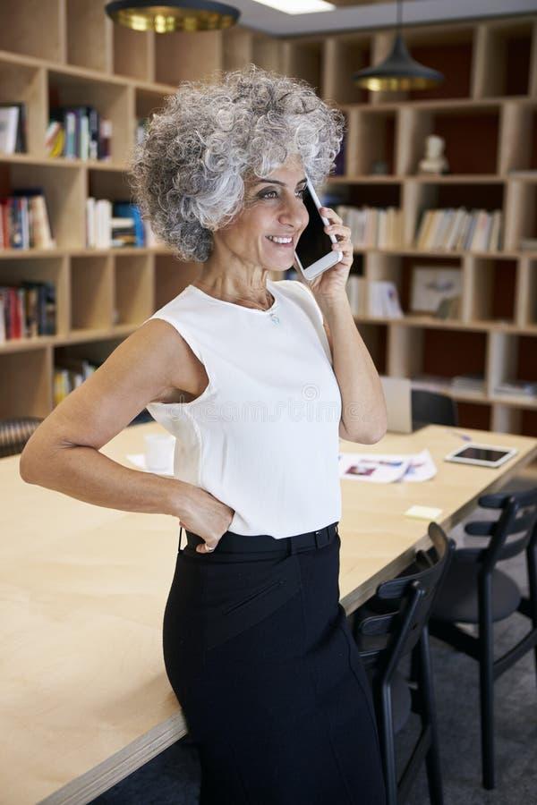 Empresaria mayor que hace llamada de teléfono en una sala de reunión fotos de archivo