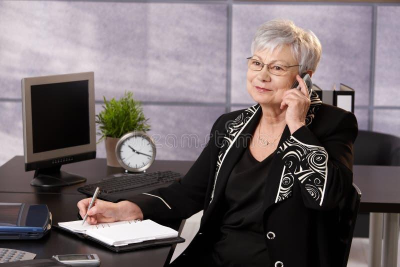 Empresaria mayor que usa el teléfono celular fotos de archivo