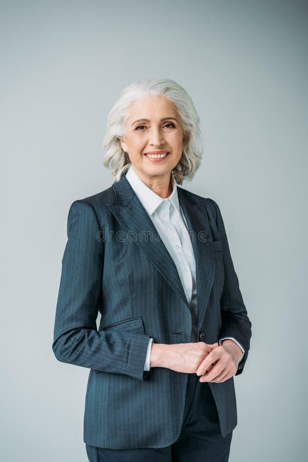 Empresaria mayor sonriente en traje en gris fotos de archivo