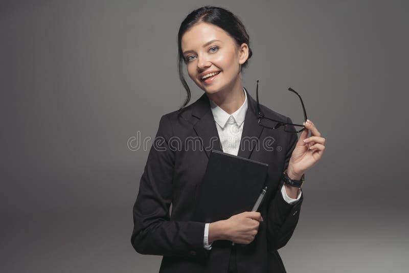 Empresaria morena en el traje negro que sostiene el diario y que sonríe en la cámara fotos de archivo