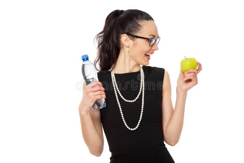 Empresaria morena en el vestido negro que sostiene la manzana y la botella o foto de archivo