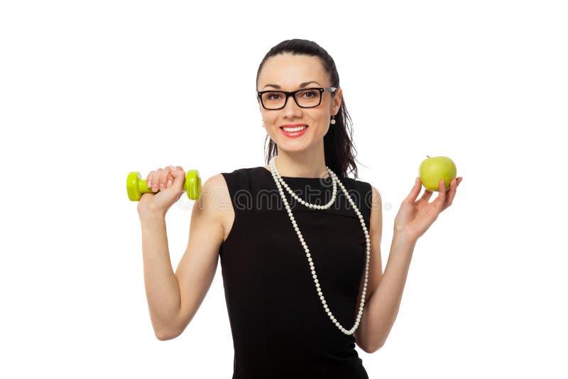 Empresaria morena que lleva a cabo la manzana y pesas de gimnasia fotografía de archivo
