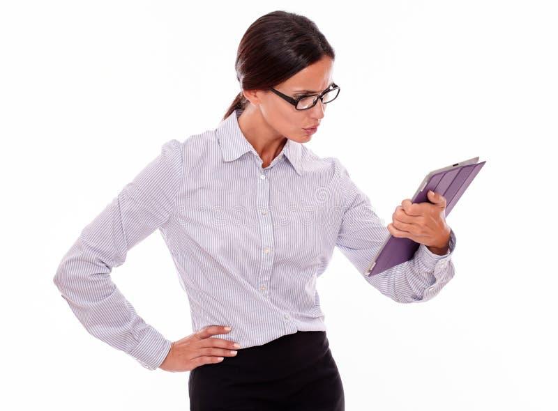 Empresaria morena subrayada que usa una tableta foto de archivo libre de regalías