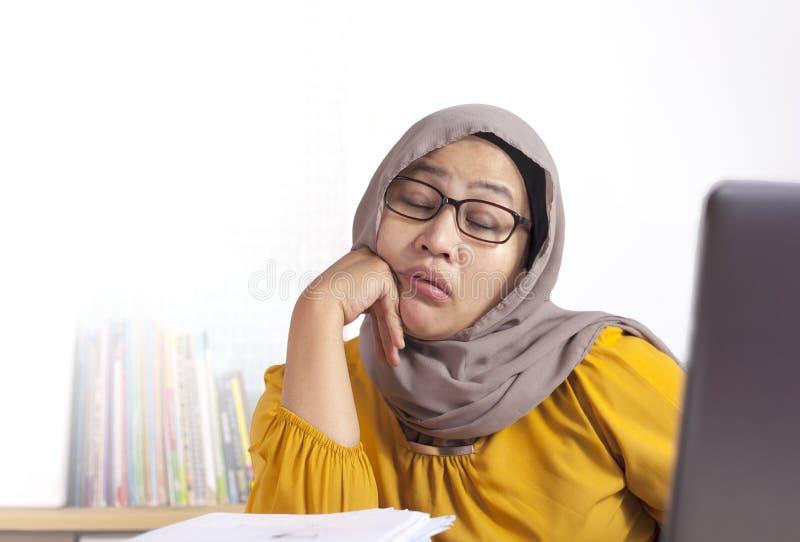 Empresaria musulm?n so?olienta cansada Waiting delante de su ordenador port?til imágenes de archivo libres de regalías