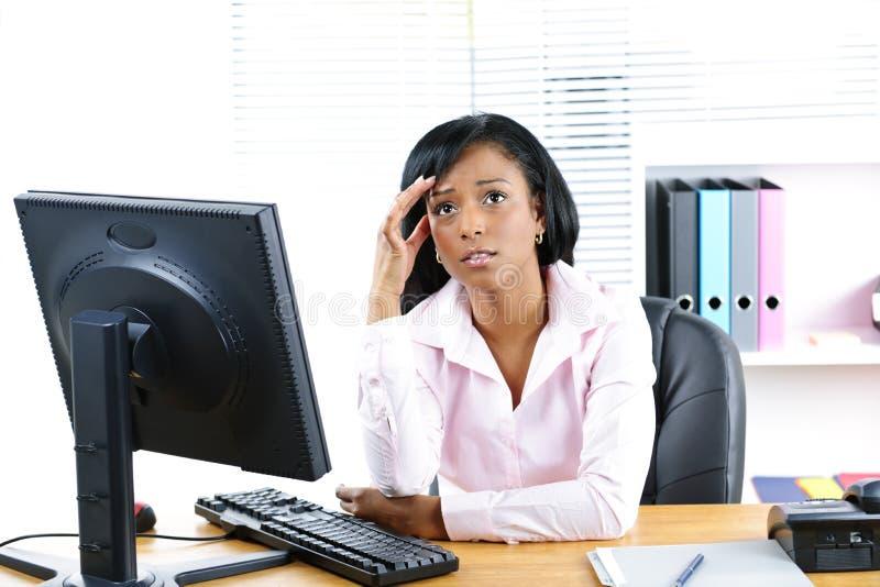 Empresaria negra preocupante en el escritorio foto de archivo