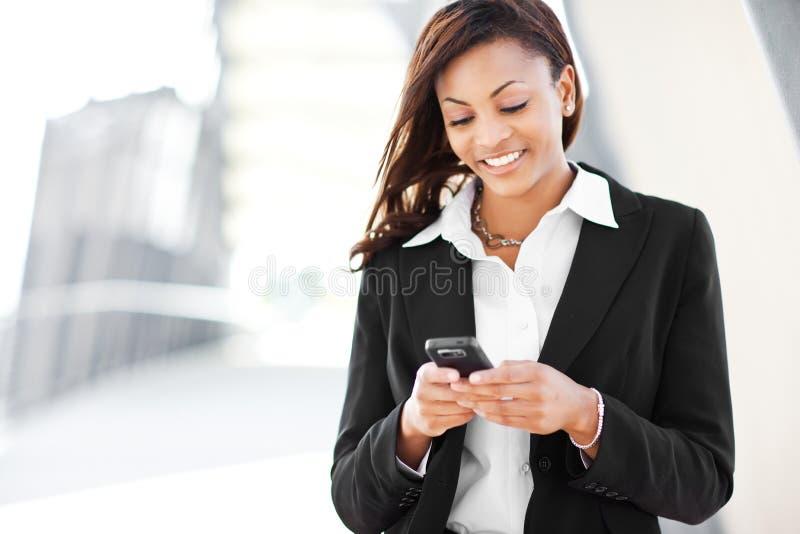Empresaria negra texting fotos de archivo libres de regalías