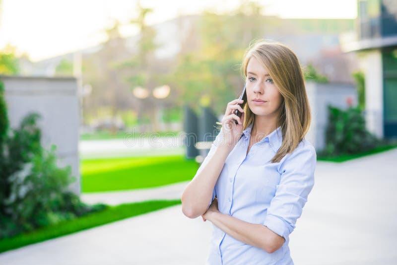 Empresaria o empresario acertada que habla en el teléfono móvil mientras que camina al aire libre fotografía de archivo