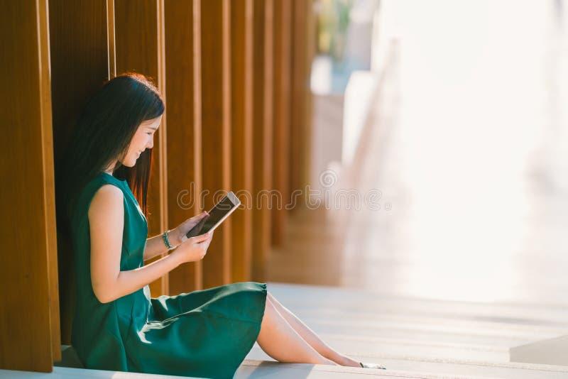 Empresaria o estudiante universitario asiática que usa la tableta digital durante puesta del sol, oficina moderna o escena de bib fotos de archivo