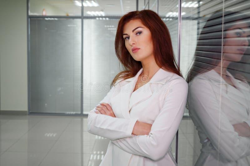 Empresaria pelirroja joven en el pasillo de la oficina que mira la cámara fotografía de archivo