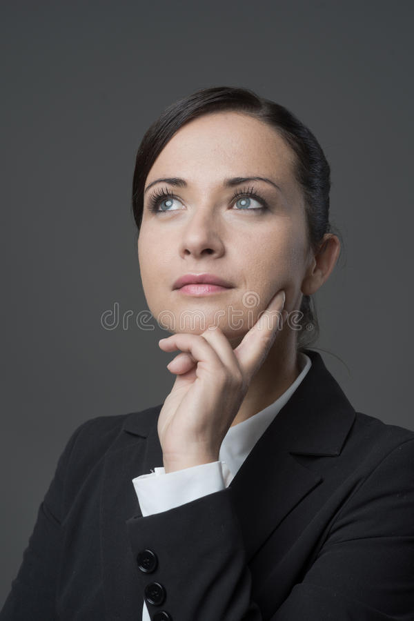 Empresaria pensativa con la mano en la barbilla imágenes de archivo libres de regalías