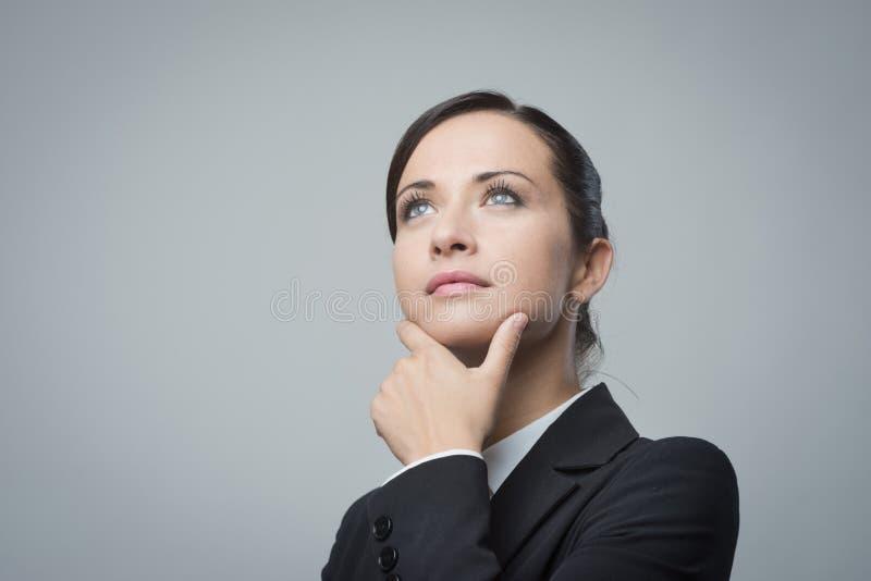Empresaria pensativa con la mano en la barbilla fotografía de archivo libre de regalías