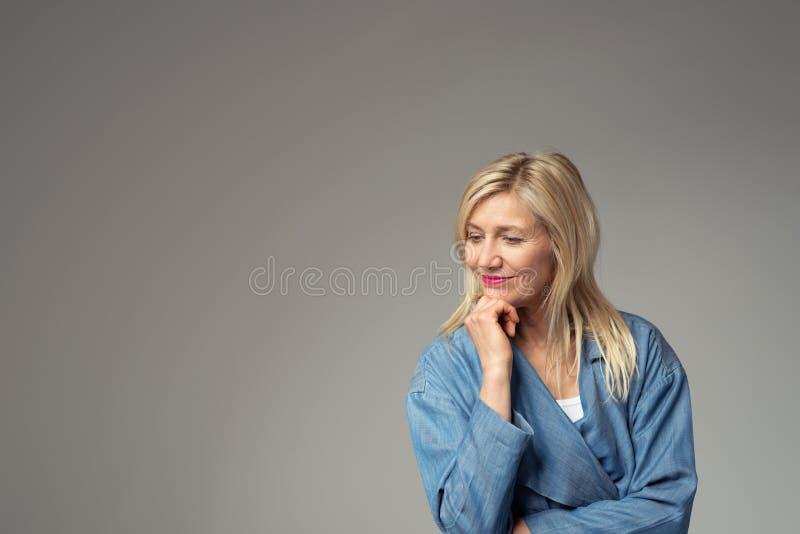 Empresaria pensativa contra fondo gris fotos de archivo