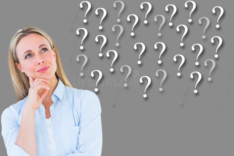 Empresaria pensativa que mira signos de interrogación contra fondo gris fotografía de archivo libre de regalías