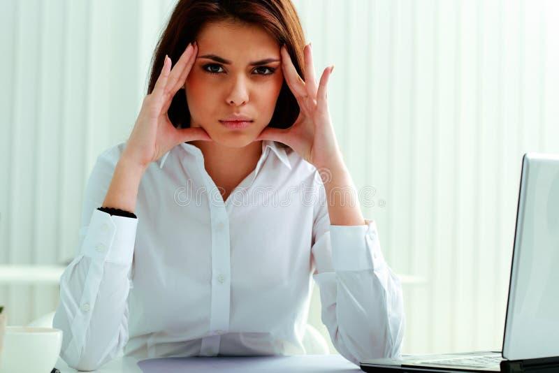 Empresaria pensativa que se sienta en la tabla foto de archivo