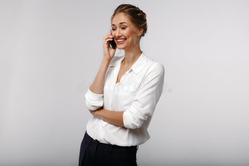 Empresaria positiva afable alegre con un teléfono celular Conversación Retrato del negocio foto de archivo libre de regalías