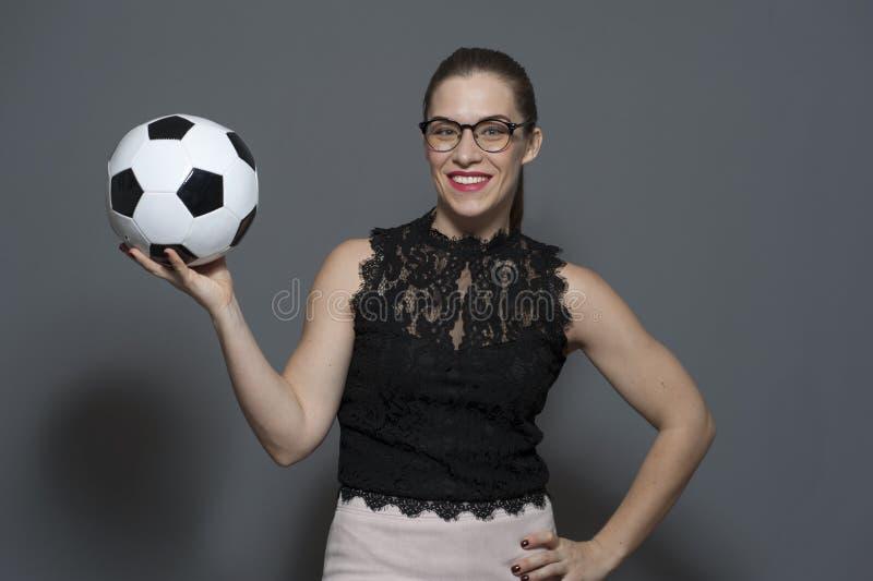 Empresaria positiva joven - fan?tico del f?tbol que sostiene el bal?n de f?tbol fotografía de archivo