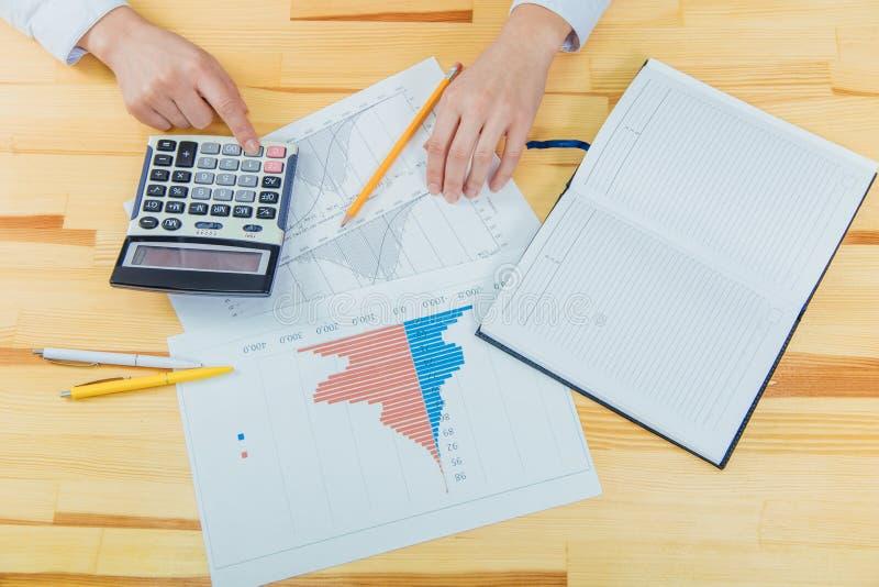 Empresaria que analiza cartas de la inversión con la calculadora para los datos financieros que analizan la cuenta fotografía de archivo