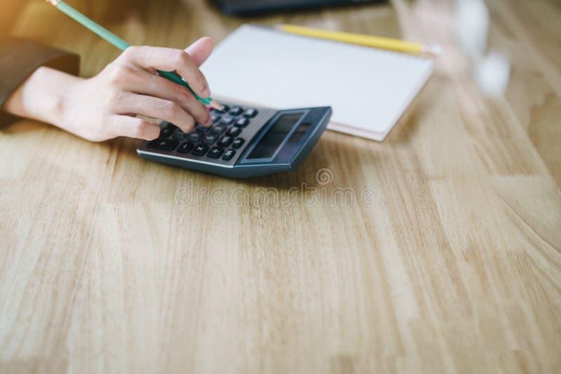 Empresaria que analiza datos del informe y el ordenador port?til en la tabla de madera Concepto de las finanzas fotografía de archivo
