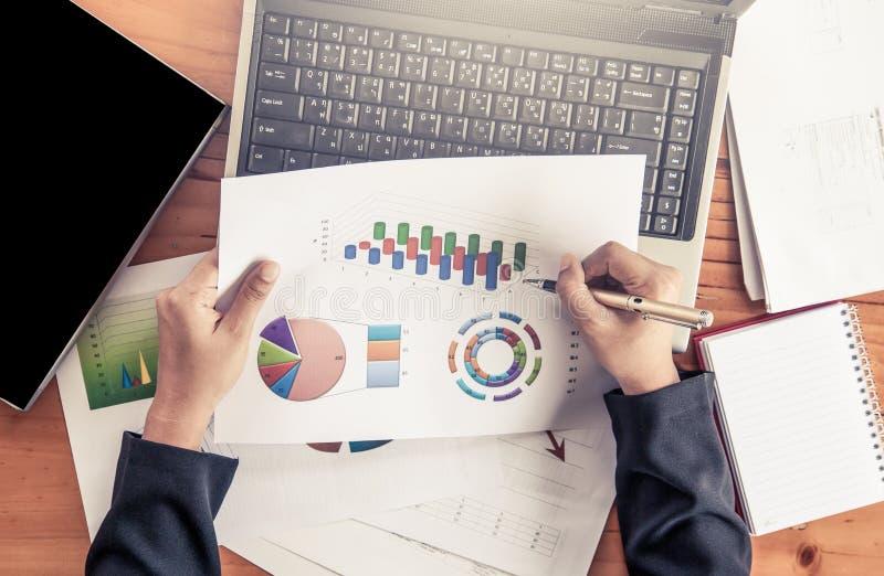 Empresaria que analiza el informe de negocios con las cartas y el gráfico imagen de archivo libre de regalías