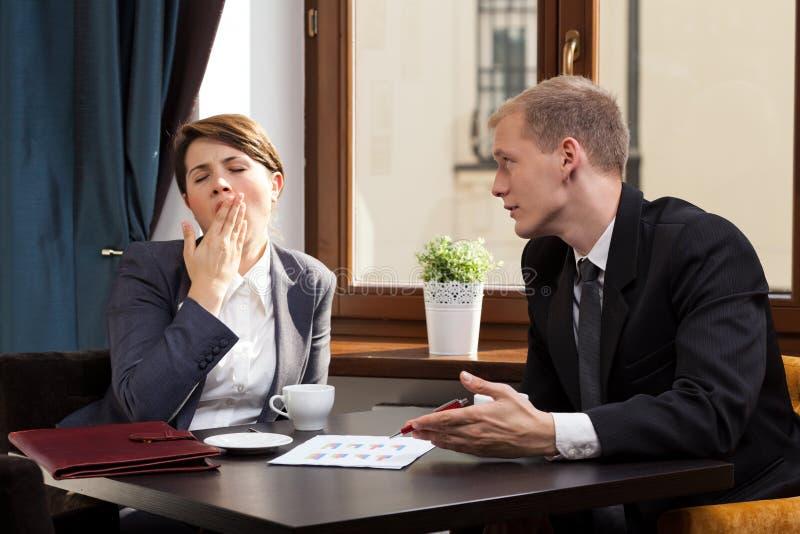 Empresaria que bosteza durante la reunión foto de archivo