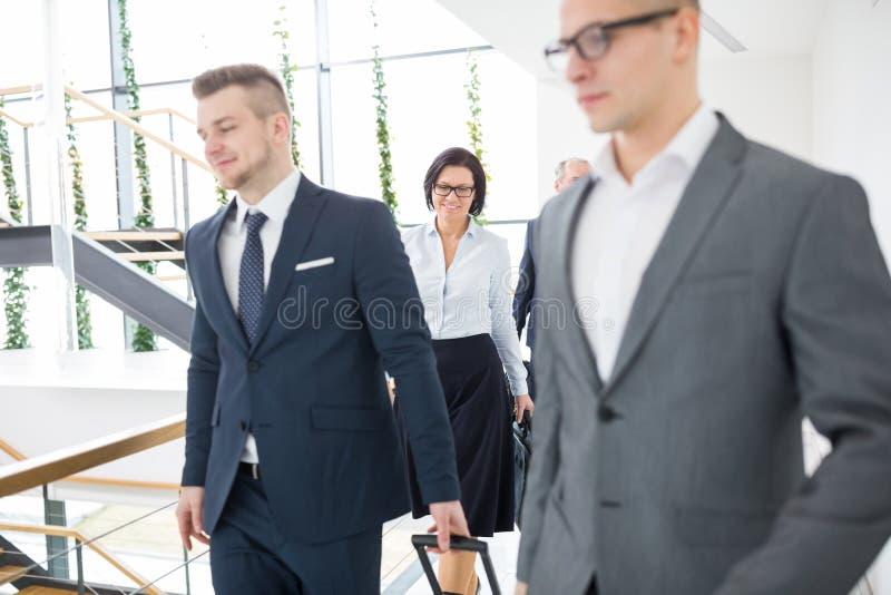 Empresaria que camina con los colegas en oficina foto de archivo